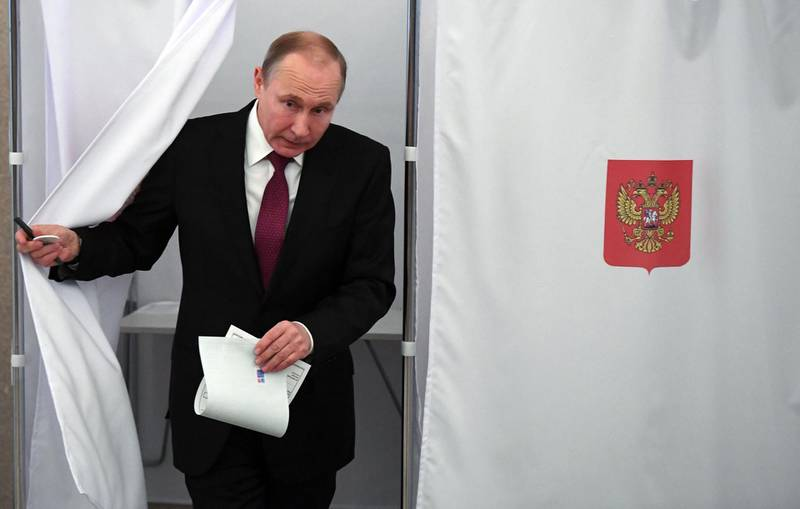 TOPSHOT - Presidential candidate, President Vladimir Putin walks out of a voting booth at a polling station during Russia's presidential election in Moscow on March 18, 2018. / AFP PHOTO / POOL / Yuri KADOBNOV