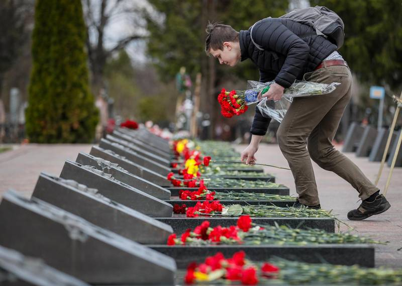 epa09161782 A man places flowers at the tombs of the victims of the Chernobyl nuclear power plant disaster at the Mitino cemetery in Moscow, Russia, 26 April 2021, on the 35th anniversary of the tragedy. The explosion of reactor 4 of the Chernobyl nuclear power plant in the early hours of 26 April 1986 is still regarded as the worst nuclear disaster to date.  EPA/YURI KOCHETKOV