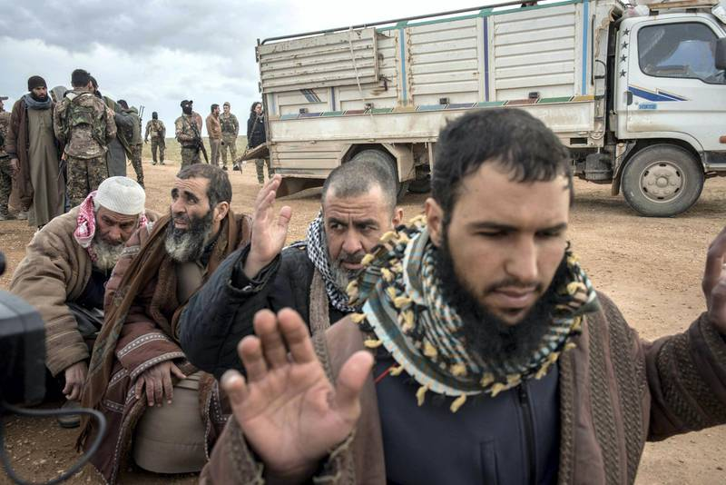 Men suspected of belonging to ISIS are screened by Syrian Democratic Forces after fleeing from the last pocket of territory held by the group outside Baghouz, Syria, 28 February 2019. Campbell MacDiarmid