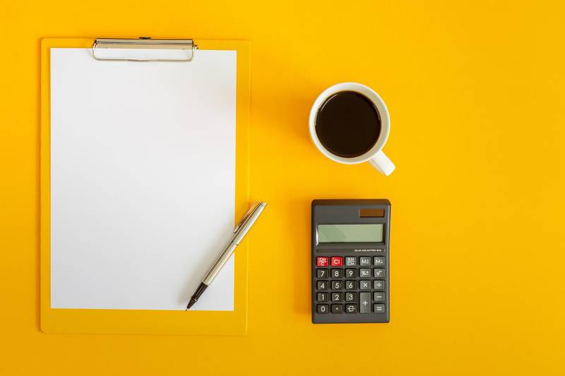 Clipboard and Calculator on Yellow Background. Getty Images
