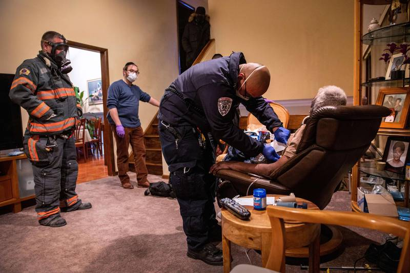 YONKERS, NEW YORK - DECEMBER 15: (EDITORIAL USE ONLY) Empress EMS Cpt. AJ Briones assesses a potential COVID-19 patient before transporting him to a hospital on December 15, 2020 in Yonkers, New York. As the coronavirus pandemic surges nationwide, hospitals have begun vaccinating healthcare workers with the Pfizer/BioNTech COVID-19 vaccine.   John Moore/Getty Images/AFP == FOR NEWSPAPERS, INTERNET, TELCOS & TELEVISION USE ONLY ==