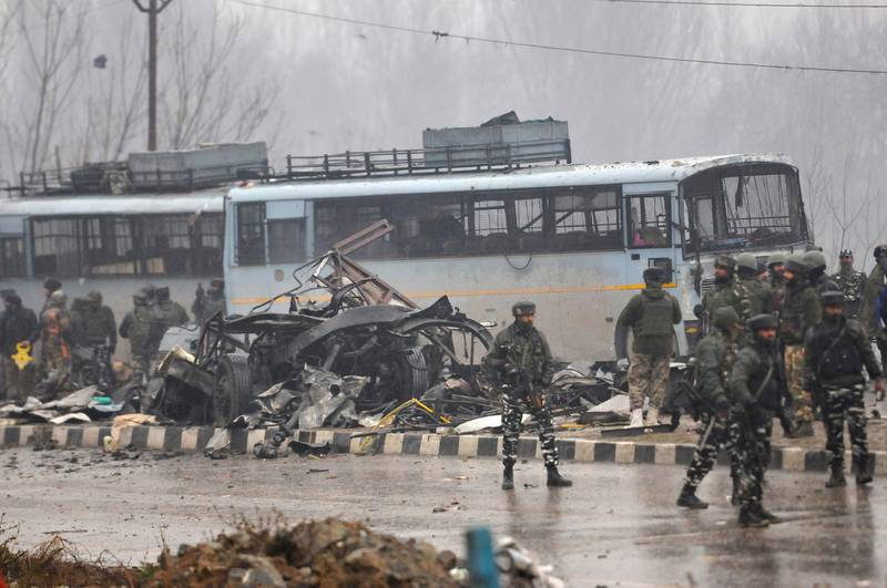 SRINAGAR, INDIA - FEBRUARY 14: Security forces near the damaged vehicles at Lethpora on the Jammu-Srinagar highway, on February 14, 2019 in Srinagar, India. At least 30 CRPF jawans were killed and many others injured in an improvised explosive device (IED) blast at Lethpora. Police sources say that the attack was likely carried out by a suicide bomber, who rammed an explosive-laden car into the CRPF bus. The bus was part of an army convoy coming from Jammu to Srinagar. (Photo by Waseem Andrabi/Hindustan Times via Getty Images)