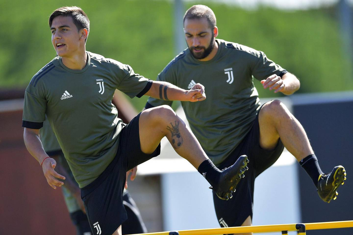 Juventus' forward Paulo Dybala (L) from Argentina and Juventus' forward Gonzalo Higuain from Argentina take part in a training session on the eve of the UEFA Champions League football match Barcelona vs Juventus on September 11, 2017 in Vinovo, near Turin. / AFP PHOTO / Marco BERTORELLO