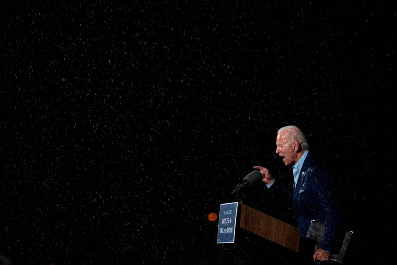 TOPSHOT - Former vice-president and Democratic presidential nominee Joe Biden delivers remarks in the rain during a Drive-In event in Tampa, Florida, on October 29, 2020. / AFP / JIM WATSON