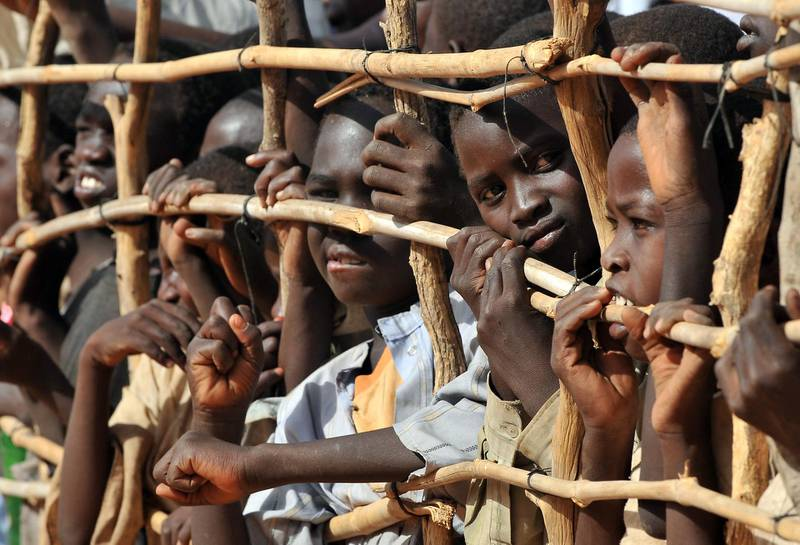 Sudanese refugee children press up against a fence in Djabal refugee camp near Goz Beida southern Chad on March 15, 2009. United Nations forces took over command from European Union peacekeepers here Sunday to protect refugees and displaced people in Chad and the Central African Republic.  The EU's EUFOR troops swapped their berets for the UN peacekeeping ones in in the eastern Chadian town of Abeche in a symbolic handover ceremony attended by senior officials and diplomats, including French Foreign Minister Bernard Kouchner. Some 5,200 peacekeepers from the UN's MINURCAT mission are now charged with protecting refugees from Sudan's strife-torn Darfur region and people displaced by a rebel insurgency in Chad and northern Central African Republic, though roughly 2,000 members of the European force will remain for a few more months under the UN beret until African and Nepalese units arrive. AFP PHOTO PHILIPPE HUGUEN (Photo by PHILIPPE HUGUEN / AFP)