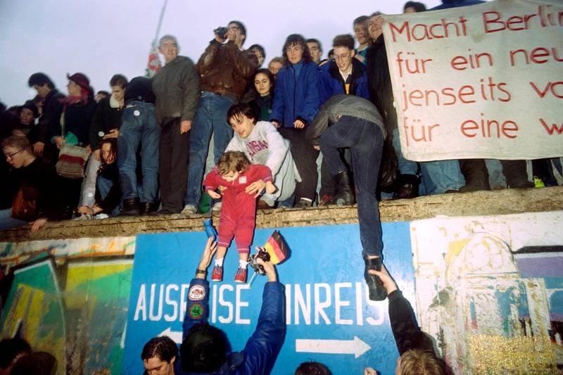 """People from East Germany greet citizens of West Germany at the Brandenburg Gate in Berlin on December 22, 1989. On November 09, Gunter Schabowski, the East Berlin Communist party boss, declared that starting from midnight, East Germans would be free to leave the country, without permission, at any point along the border, including the crossing-points through the Wall in Berlin. The Berlin concrete wall was built by the East German government in August 1961 to seal off East Berlin from the part of the city occupied by the three main Western powers to prevent mass illegal immigration to the West. According to the """"August 13 Association"""" which specialises in the history of the Berlin Wall, at least 938 people - 255 in Berlin alone - died, shot by East German border guards, attempting to flee to West Berlin or West Germany. PATRICK HERTZOG (Photo by PATRICK HERTZOG / AFP)"""