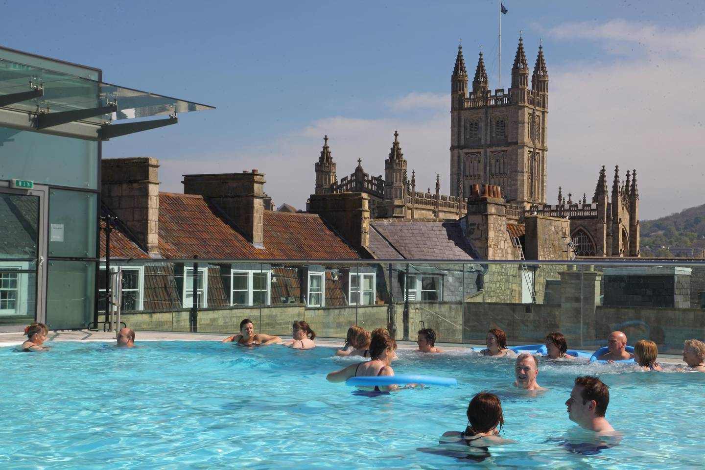 BATH, ENGLAND - APRIL 21:  Visitors enjoy the sunshine as they swim in the rooftop pool of the Thermae Bath Spa on April 21, 2009 in Bath, England. Despite the global economic downturn, visitors to the historic Unesco World Heritage city's attractions - including the 40million GBP Spa development and the only place in Britain where you can bathe in natural hot spring waters - have held steady, helped in part by the weakness of the pound encouraging foreigners to visit Britain, and British holidaymakers to stay at home. In 2007, nearly 4 million visitors earned the city's tourism industry 432 million GBP and early indicators suggest that the figures will be very similar for this year.  (Photo by Matt Cardy/Getty Images) *** Local Caption ***  WK30AU-TR-THARMAESPA02.jpg