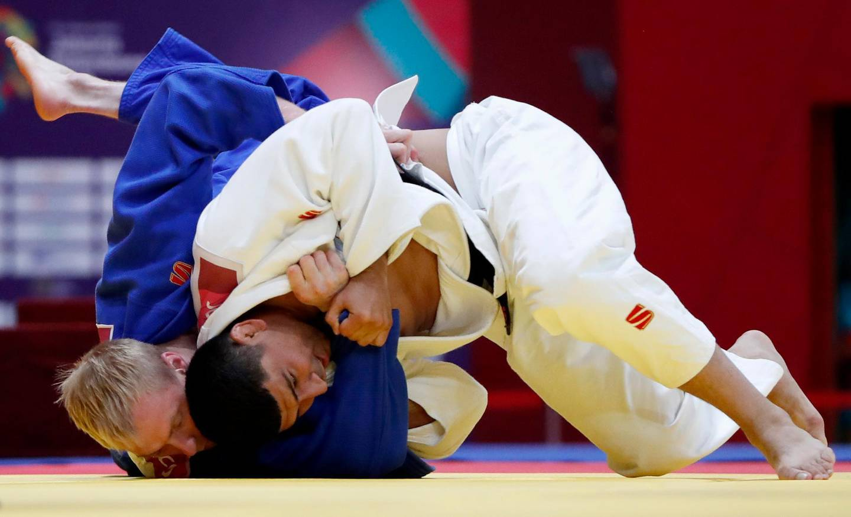 Judo - 2018 Asian Games - Men's -100kg, Contest for Bronze Medal - JCC Plenary Hall, Jakarta, Indonesia - August 31, 2018 - Sherai Juraev of Uzbekistan in action with Ivan Remarenco of United Arab Emirates. REUTERS/Issei Kato