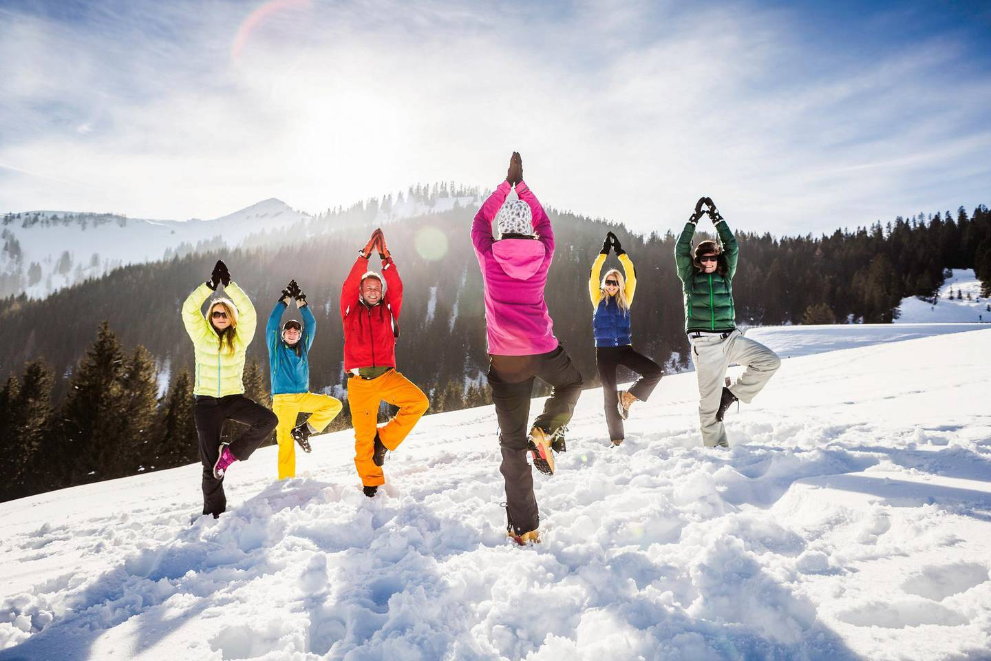 Group of friends doing yoga in snow