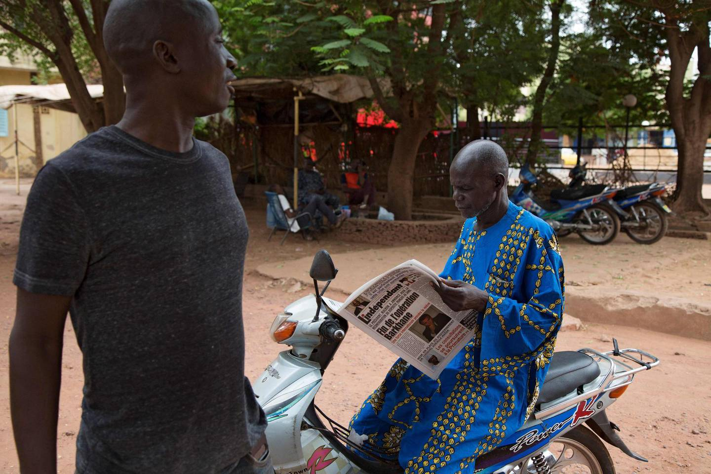 """A man buys a newspaper whose headlines announce a major drawdown of France's military presence in the Sahel, where forces have been battling jihadist insurgents for nearly a decade, in Bamako on June 11, 2021. French President announced on June 10, 2021 that the existing Barkhane operation would end, with France's presence becoming part of the so-called Takuba international task force in which """"hundreds"""" of French soldiers would form the """"backbone"""". / AFP / ANNIE RISEMBERG"""