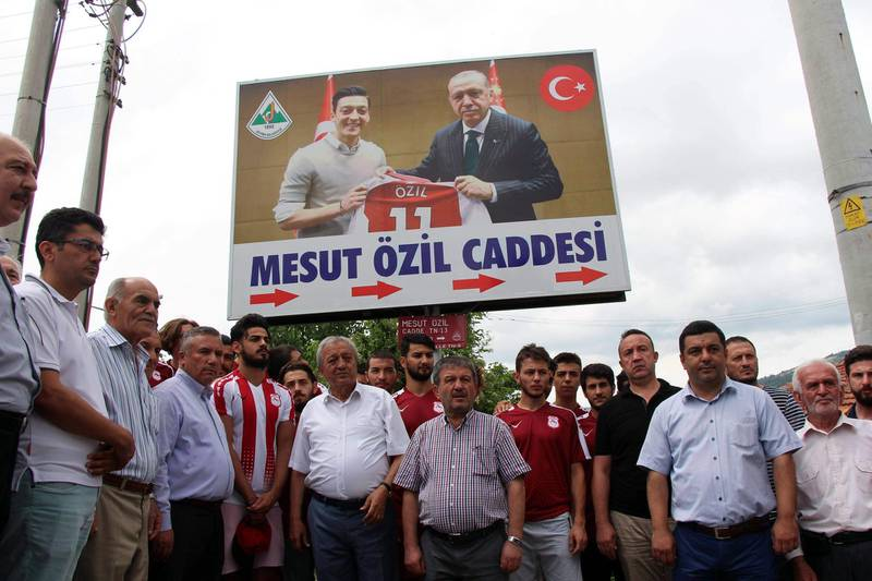 """People gather under a cardboard bearing a photo of German national team football player Mesut Ozil (L) and Turkish President Recep Tayyip Erdogan (R) reading """" Mesut Ozil street"""" on July 24, 2018 during a street name ceremony in Zonguldak's Devrek district.  Turkey OUT  / AFP / Demiroren News Agency / -"""