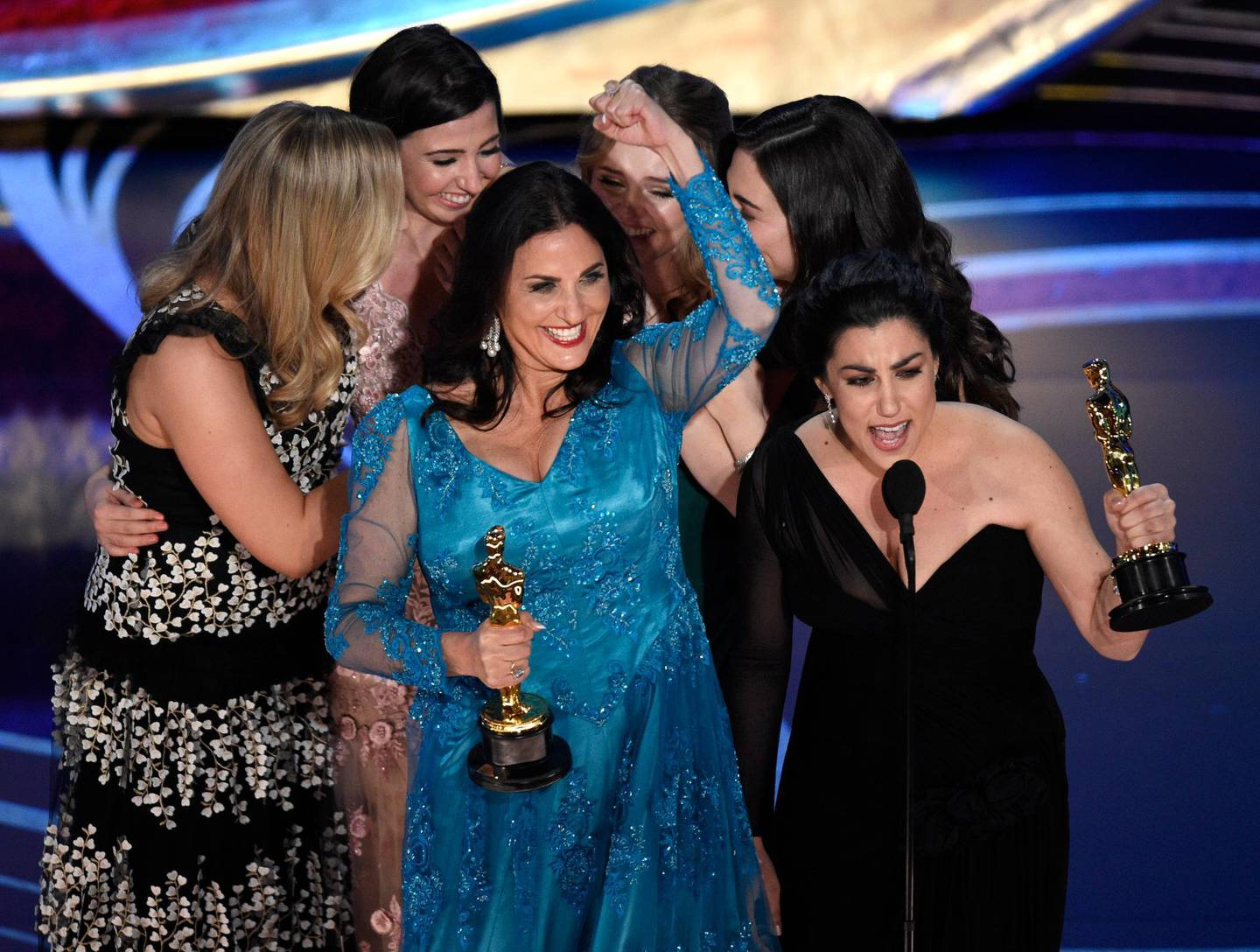 """Melissa Berton, center left, and Rayka Zehtabchi accept the award for best documentary short subject for """"Period. End of Sentence."""" at the Oscars on Sunday, Feb. 24, 2019, at the Dolby Theatre in Los Angeles. (Photo by Chris Pizzello/Invision/AP)"""