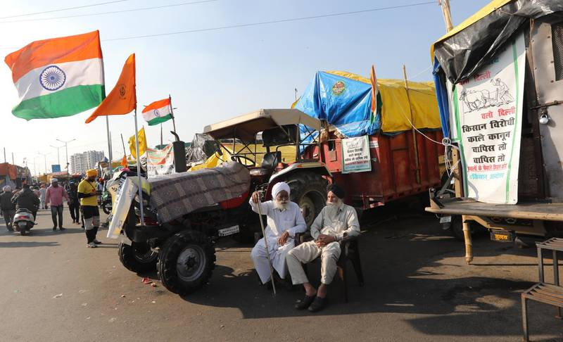 epa08991369 Indian farmers sit next to their tractors during a protest at the Delhi Ghazipur Border near New Delhi, India, 06 February 2021. Farmers announced nationwide 'Chakka Jam' or road blockade after Thousands of farmers gathered and tried to cross the sealed New Delhi border points to hold protests against the government's new agricultural laws and to demand for repealing the laws. Farmers have been stopped by the police at the various points outside the Delhi border, which are connected with neighbouring states of Haryana and Uttar Pradesh, and since then farmers have been holding sit-in protests there.  EPA/RAJAT GUPTA