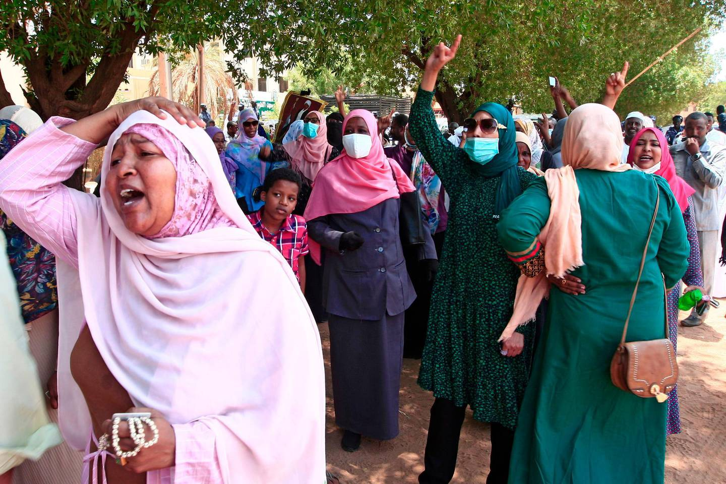 Family members of the accused rally outside the Khartoum courthouse during a trial session of Sudan's ousted president Omar al-Bashir along with others, in the Sudanese capital on August 25, 2020. The trial of Sudan's ousted president Omar al-Bashir, on charges related to the coup that brought him to power in 1989, was adjourned to September 1, the judge said.  / AFP / ASHRAF SHAZLY