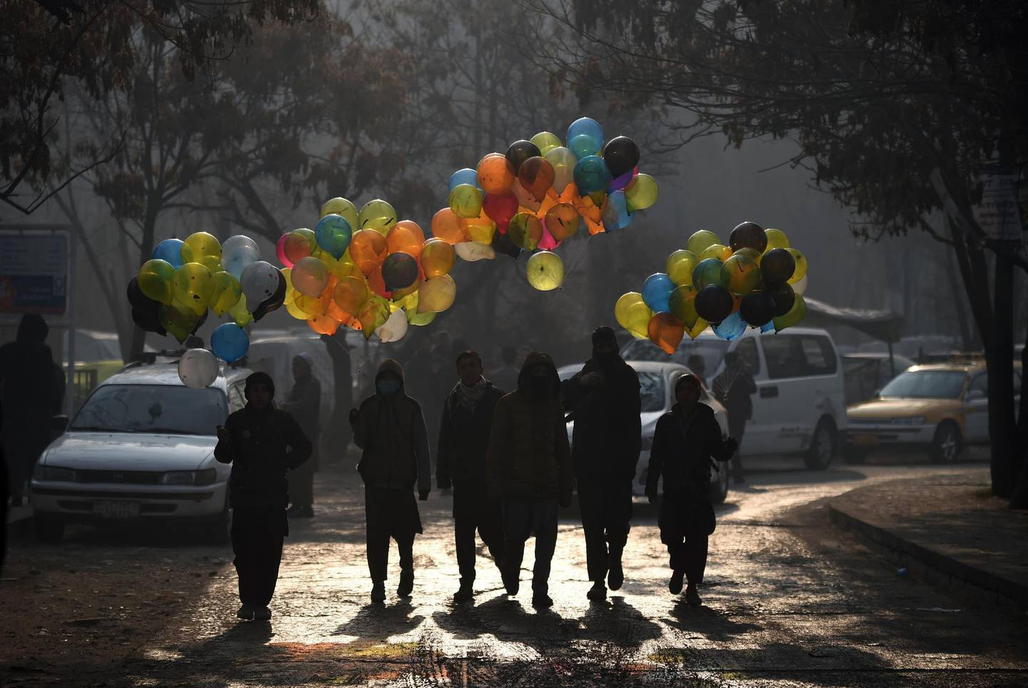 Afghan balloon vendors walks past the Ministry of Public Works a day after a deadly militant attack in Kabul on December 25, 2018. An hours-long gun and suicide attack on a Kabul government compound killed at least 43 people, the health ministry said December 25, making it one of the deadliest assaults on the Afghan capital this year.  / AFP / WAKIL KOHSAR