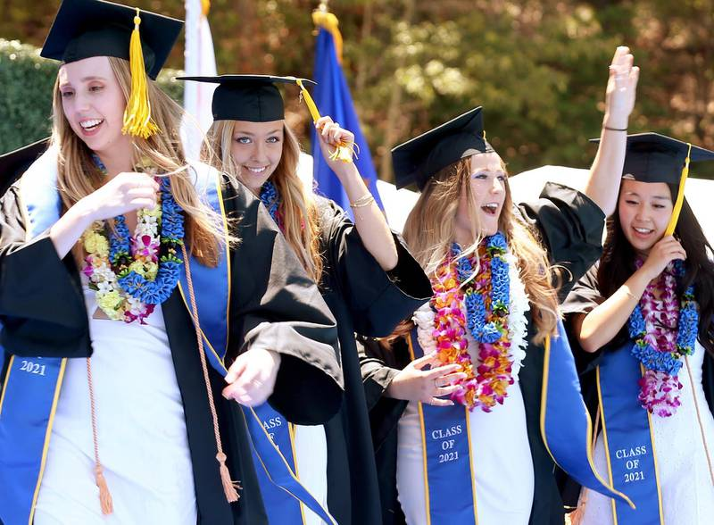 WESTWOOD, CALIFORNIA - JUNE 11: Graduating UCLA students celebrate while walking the stage for their commencement ceremony at Drake Stadium on June 11, 2021 in Westwood, California. Up to 230 students per hour were able to participate in the graduate procession. Each graduate was allowed two guests and were permitted to remove their masks before crossing the stage.   Mario Tama/Getty Images/AFP == FOR NEWSPAPERS, INTERNET, TELCOS & TELEVISION USE ONLY ==