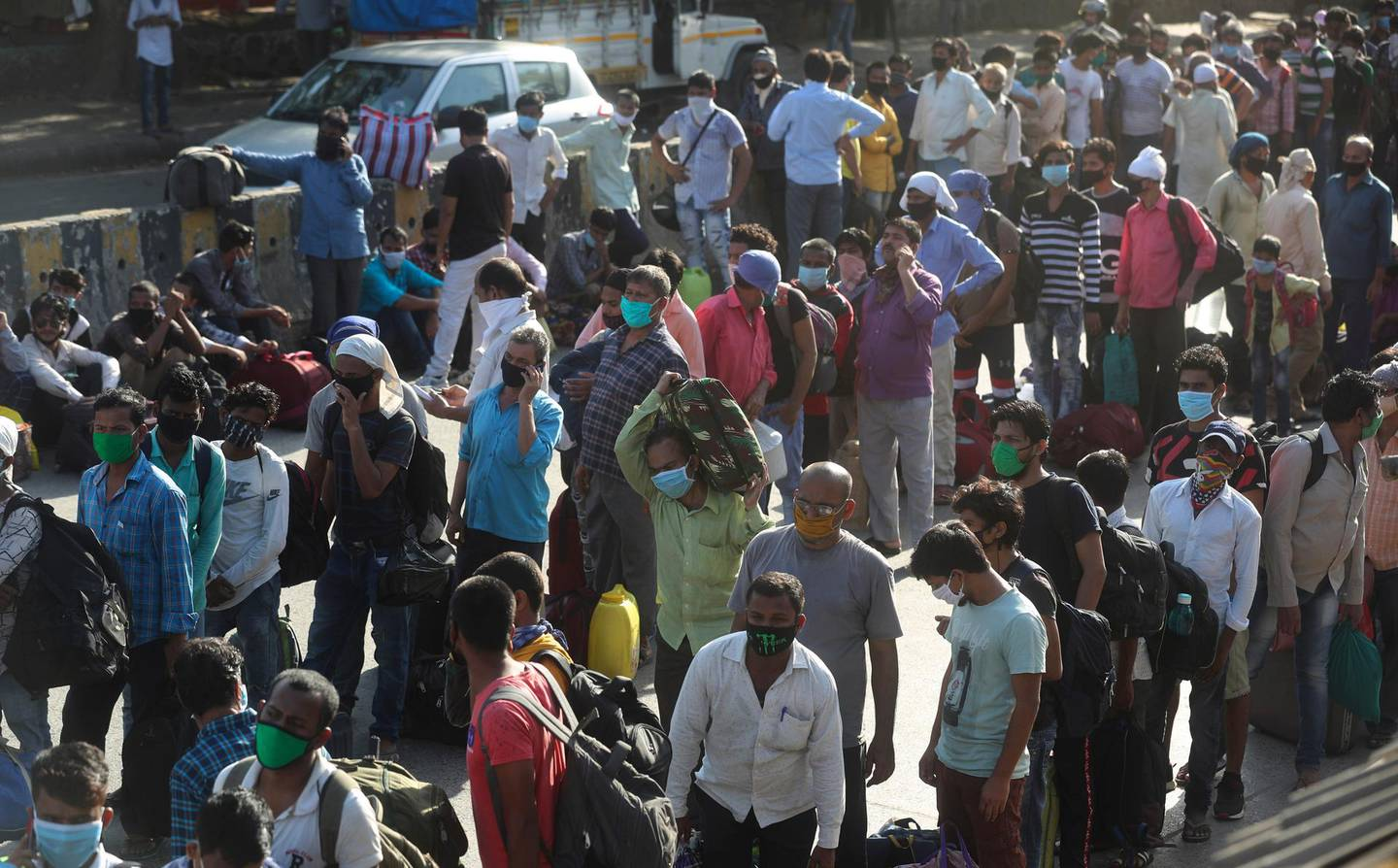 Migrant workers line up to board buses for their onward journey by train to their home states, at Dharavi, one of Asia's largest slums, in Mumbai, India, Friday, May 22, 2020. India's lockdown was imposed on March 25 and has been extended several times. On May 4, India eased lockdown rules and allowed migrant workers to travel back to their homes, a decision that has resulted in millions of people being on the move for the last two weeks. (AP Photo/Rafiq Maqbool)