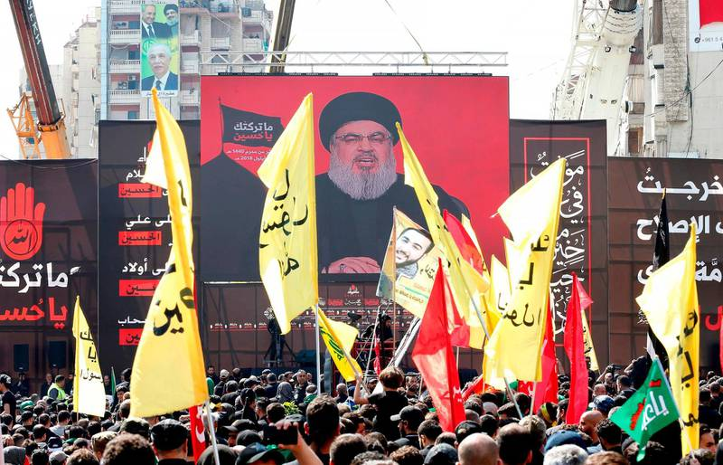 Supporters of Lebanon's Shiite movement Hezbollah gather near a giant poster of their leader Hassan Nasrallah during a ceremony to mark Ashura on September 20, 2018 in Beirut. Ashura commemorates the death of Imam Hussein, grandson of the Muslim faith's prophet Mohammed, who was killed by the armies of his rival Yazid over the succession for the caliphate near Karbala in 680 AD. / AFP / ANWAR AMRO