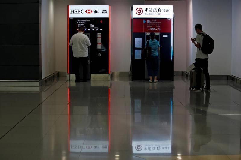 FILE PHOTO: People use HSBC and Bank of China ATM machines at Hong Kong Airport in Hong Kong, China September 5, 2017. REUTERS/Bobby Yip/File Photo