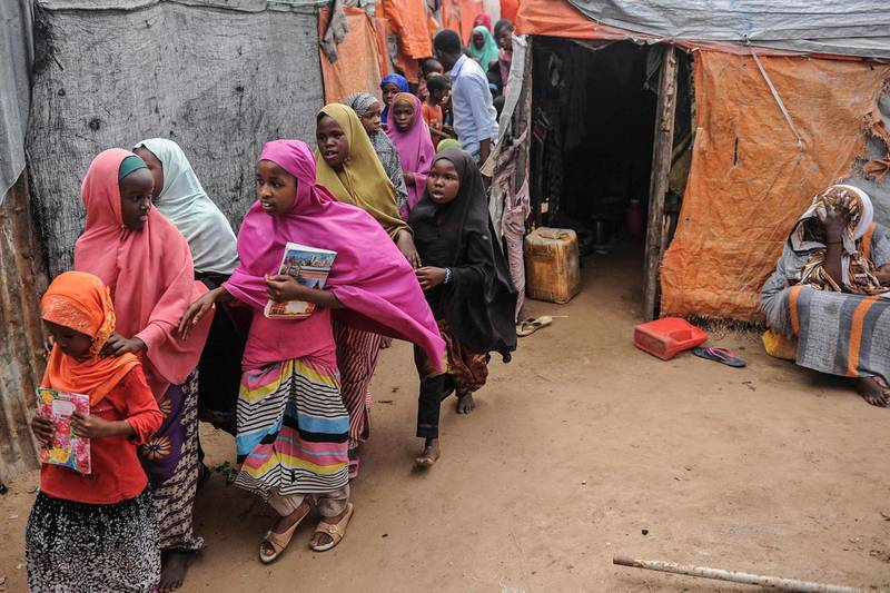 Displaced Somali children and teenagers leave after attending a class to learn alphabets and numbers at a makeshift school at the Badbado IDP camp in Mogadishu, Somalia, on June 25, 2018.  University Students from various universities provide voluntarily free schooling to about 600 girls and boys under 16 at various IDP camps in Mogadishu since May 2017. / AFP / Mohammed ABDIWAHAB