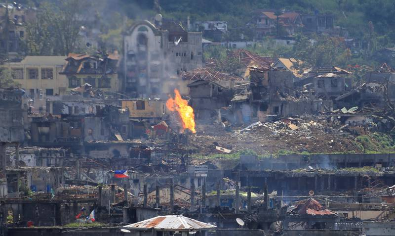 Flame rises as damaged buildings are seen after government troops cleared the area from pro-Islamic State militant groups inside a war-torn area in Marawi city, southern Philippines October 23, 2017. REUTERS/Romeo Ranoco