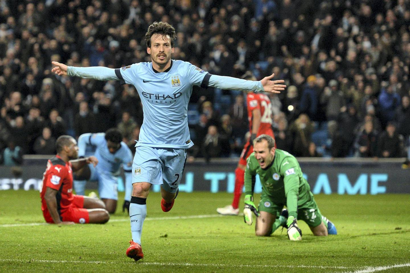 """Manchester City's Spanish midfielder David Silva celebrates scoring the opening goal as Leicester City's Australian goalkeeper Mark Schwarzer reacts (R) during the English Premier League football match between Manchester City and Leicester City at the Etihad Stadium in Manchester, north west England, on March 4, 2015. AFP PHOTO / OLI SCARFF  RESTRICTED TO EDITORIAL USE. NO USE WITH UNAUTHORIZED AUDIO, VIDEO, DATA, FIXTURE LISTS, CLUB/LEAGUE LOGOS OR """"LIVE"""" SERVICES. ONLINE IN-MATCH USE LIMITED TO 45 IMAGES, NO VIDEO EMULATION. NO USE IN BETTING, GAMES OR SINGLE CLUB/LEAGUE/PLAYER PUBLICATIONS. (Photo by OLI SCARFF / AFP)"""