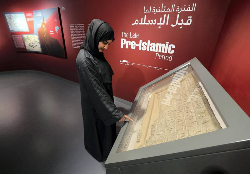 Sharjah, United Arab Emirates - July 10, 2019: Weekend's postcard section. Amna Albadri looks at a tombstone featuring bi-lingual funerary inscription in Aramaic and ancient South Arabian script, found in Mleiha at the Mleiha Archaeological Centre. Wednesday the 10th of July 2019. Maleha, Sharjah. Chris Whiteoak / The National