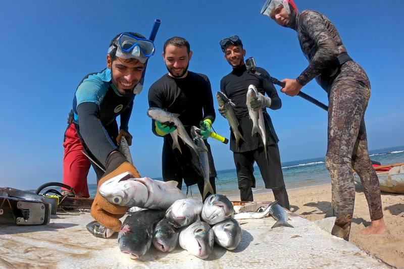 Palestinian spear-fisherman Ashraf Al-Amoudi displays fish on a beach in the southern Gaza Strip, October 8, 2020. Picture taken October 8, 2020. REUTERS/Suhaib Salem