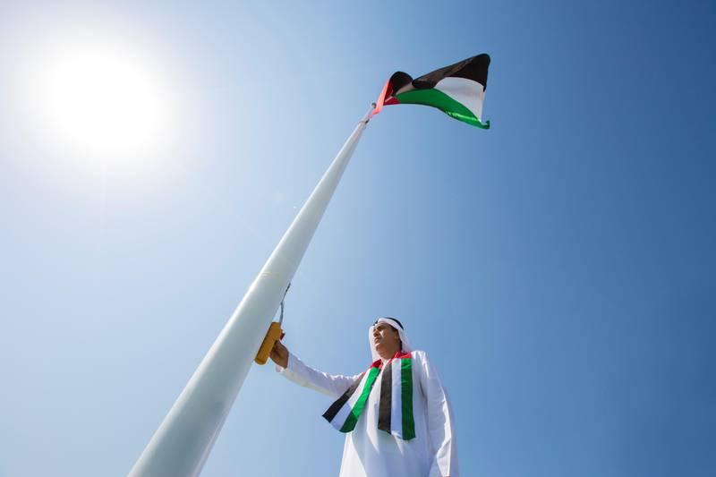 ABU DHABI, UNITED ARAB EMIRATES - November 02, 2017: ABU DHABI, UNITED ARAB EMIRATES - November 02, 2017: HE Jaber Al Suwaidi, General Director of the Crown Prince Court - Abu Dhabi (C), raises the UAE flag during a Flag Day ceremony, at the Crown Prince Court of Abu Dhabi.  ( Hamad Al Kaabi / Crown Prince Court - Abu Dhabi ) —