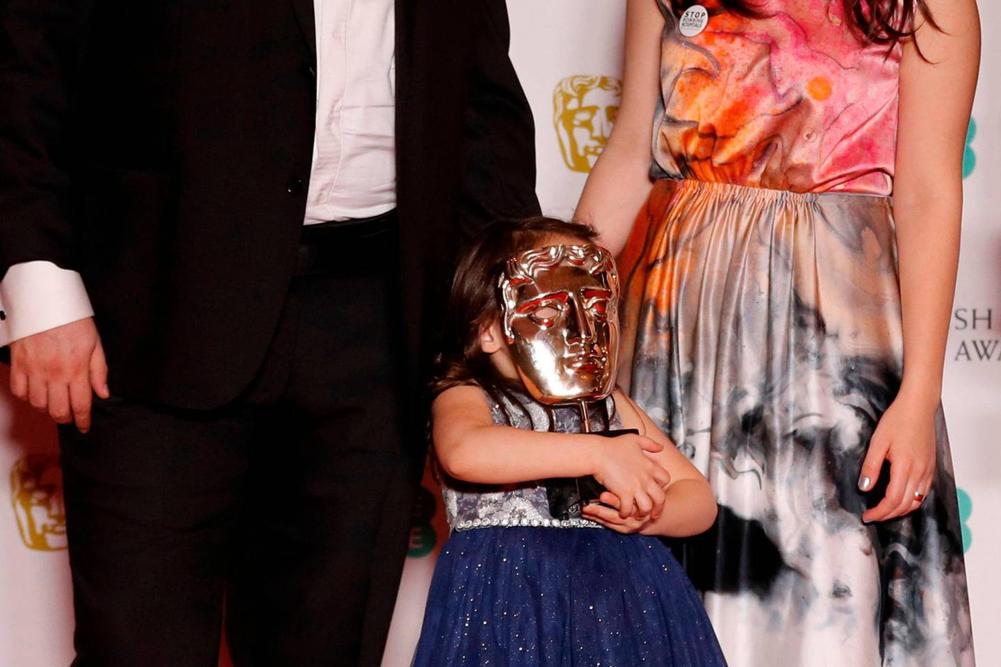 Sama (C) holds the award over her face as (L-R) Hamza al-Kateab and Syrian filmmaker Waad al-Kateab pose during the award for a Documentary for 'For Sama' at the BAFTA British Academy Film Awards at the Royal Albert Hall in London on February 2, 2020.   / AFP / Adrian DENNIS