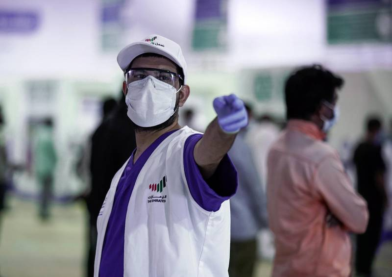 Abu Dhabi, United Arab Emirates, May 6, 2020. the new Ambulatory Healthcare Services, a SEHA Health System Facility, National Screening Project in Mussafah Industrial Area in Abu Dhabi.   -- A staff member of the center directs a workers to the next area at the screening center.Victor Besa / The NationalSection:  NAReporter:  Nick Webster
