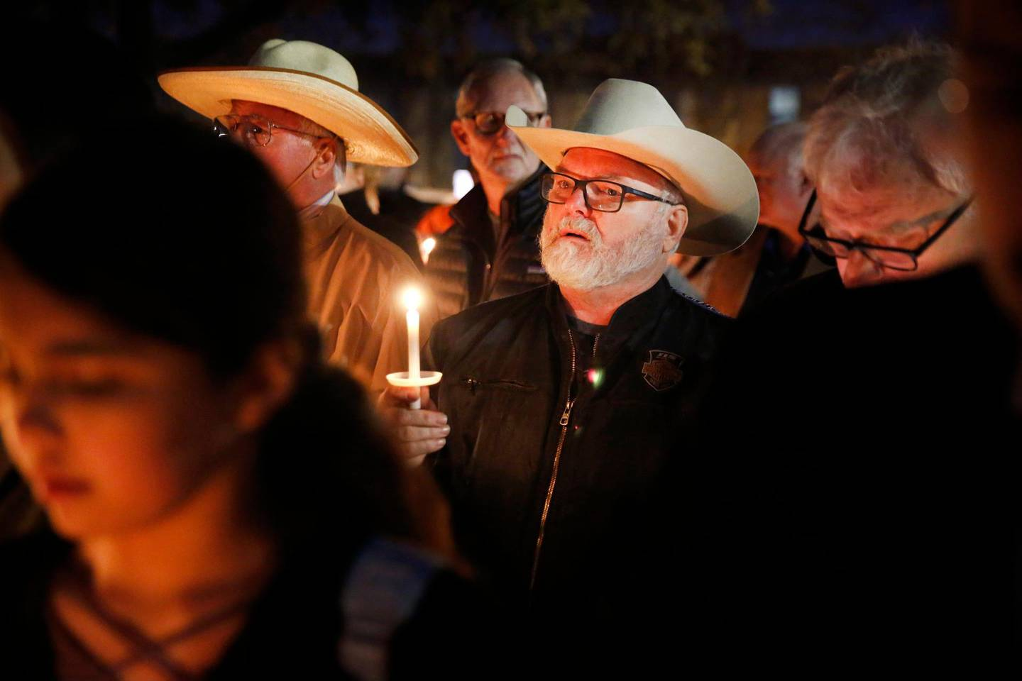 Stephen Willeford, center, who confronted and exchanged gunfire with the Sutherland Springs church shooter in 2017, joins church and community members gathered outside West Freeway Church of Christ for a candlelight vigil, Monday, Dec. 30, 2019, in White Settlement, Texas. A gunman shot and killed two people before an armed security officer returned fire, killing him during a service at the church on Sunday. (Tom Fox/The Dallas Morning News via AP)