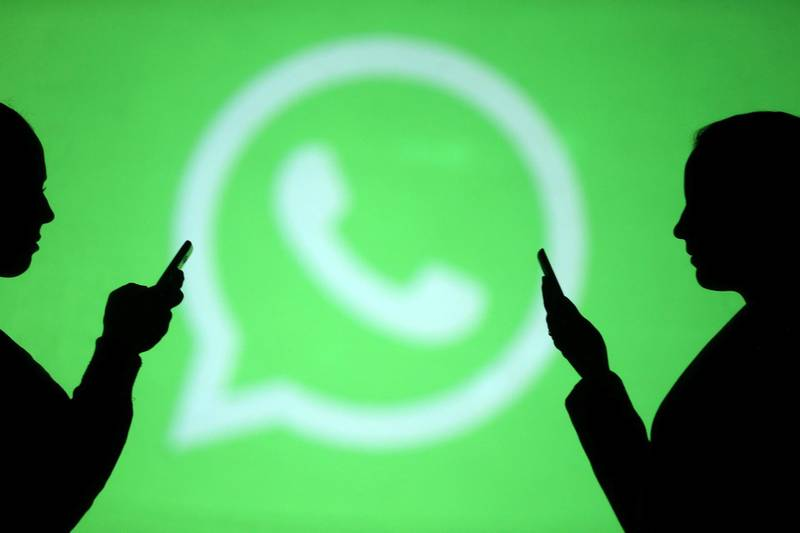 REFILE - CLARIFYING CAPTION Silhouettes of mobile users are seen next to a screen projection of Whatsapp logo in this picture illustration taken March 28, 2018.  REUTERS/Dado Ruvic/Illustration