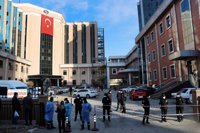 Police and medics gather outside the privately-run Sanko University Hospital in Gaziantep, southeastern Turkey, Saturday, De. 19, 2020. A fire broke out Saturday at an intensive care unit treating COVID-19 patients in southern Turkey after an oxygen cylinder exploded, killing several people, state-run media reported. (Kadir Gunes/DHA via AP)