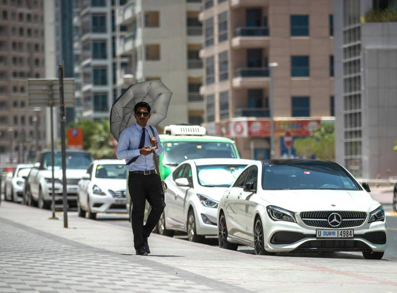 Dubai, U.A.E., June 11,2018.Extreme warm weather at the Dubai Marina area.   A pedestrian uses an umbrella to shield himself from the sun.Victor Besa / The NationalSection:  National