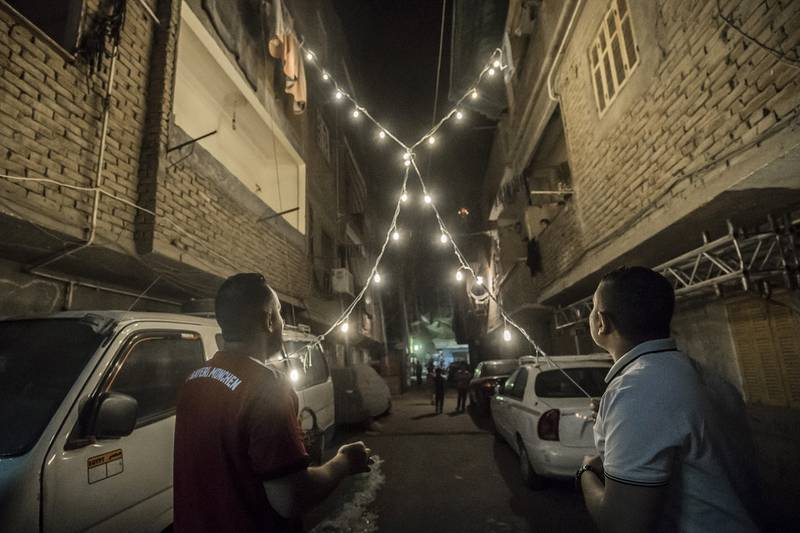 Egyptian youths decorate their residential street in preparation for the Muslim holy month of Ramadan in Cairo's Hadayek el-Maadi district, on April 21, 2020. - From cancelled iftar feasts to suspended mosque prayers, Muslims across the Middle East are bracing for a bleak month of Ramadan fasting as the threat of the COVID-19 pandemic lingers. Ramadan is a period for both self-reflection and socialising. Believers fast from dawn to dusk and then gather around a family or community meal each evening of Islam's holiest month, which begins later this week and ends with Eid al-Fitr festivities (Photo by Khaled DESOUKI / AFP)
