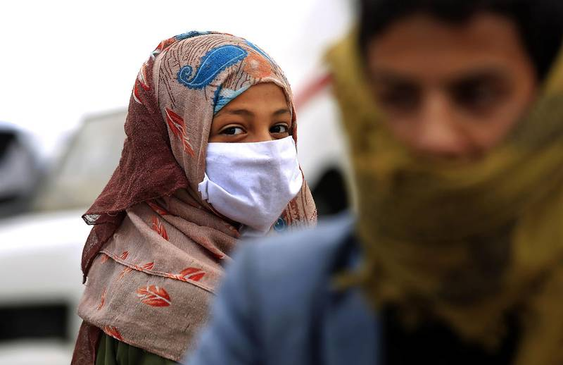 A woman wearing a protective face mask walks in a street in the capital Sanaa, amid concerns over the spread of the novel coronavirus, on March 28, 2020. Yemen's broken healthcare system has not so far recorded a case of the COVID-19 illness, but aid groups have warned that when it does hit, the impact will be catastrophic in a country already regarded as facing the world's worst humanitarian crisis. / AFP / Mohammed HUWAIS