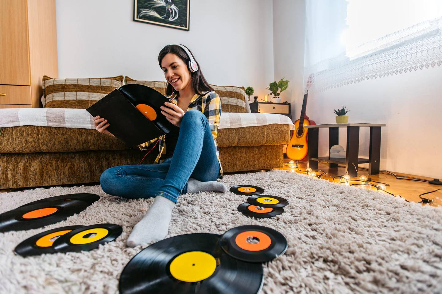 Young beautiful woman is listening old time records at home in lockdown.