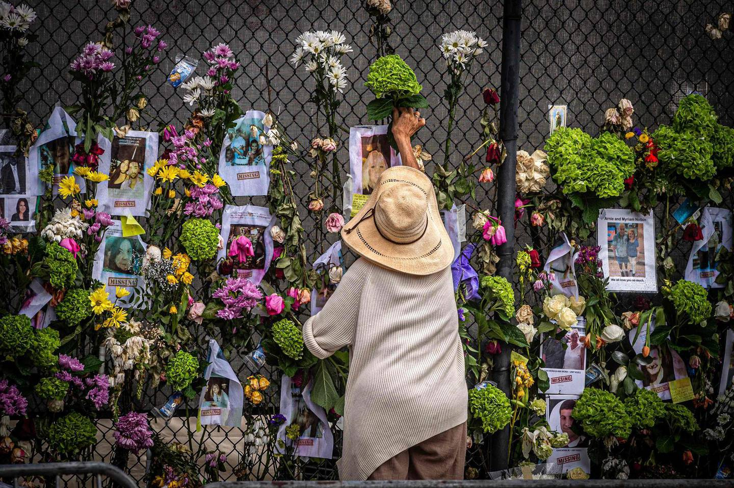 A woman adds flowers to a memorial featuring photos of some of those lost in the partially collapsed 12-story Champlain Towers South building on June 28, 2021 in Surfside, Florida. Questions mounted Monday about how a residential building in the Miami area could have collapsed so quickly and violently last week, as the death toll rose to 11 with 150 still unaccounted for, and desperate families feared the worst. / AFP / Giorgio Viera