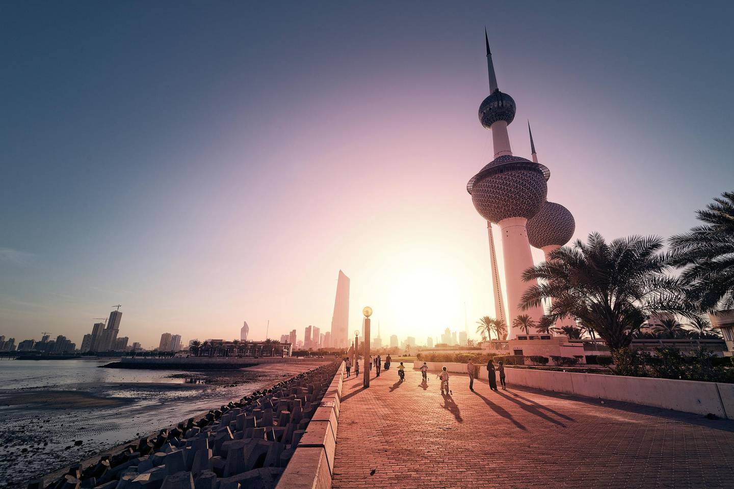 View of Kuwait Towers with Kuwait City in the background at sunset.