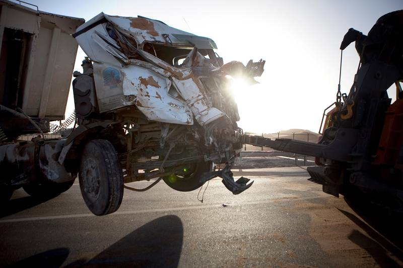 Al Ain, United Arab Emirates, February 4, 2013:  The remnants of a truck are hauled away from the scene of a tragic traffic accident, which involved a truck and a bus full of laborers and has left 22 people dead and sent many to a hospital, on Monday early evening, Feb. 4, 2013, at the scene of the accident, about 35km from Al Ain on the Abu Dhabi - Al Ain road. The accident happened at 7:30am as the bus, loaded with 45 workers, 95 percent of which were reported Bangladeshi, carried the people to their work at a nearby palace. The bus travelers were employees of the Al Hakeem Decorations and have worked at the palace as maintenance crew. Silvia Razgova / The National