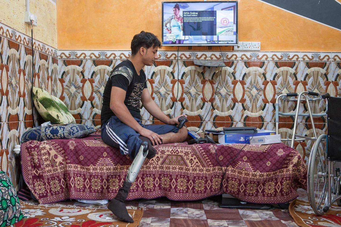 Jasim Abdulameer, 22, a former Iraqi Hashd Al Shaabi fighter, got injured during a military operation against the Islamic State. Amputee and jobless, Abdulameer lives now at his parent's house, in Basra, a major city in south Iraq. Photo by Sebastian Castelier