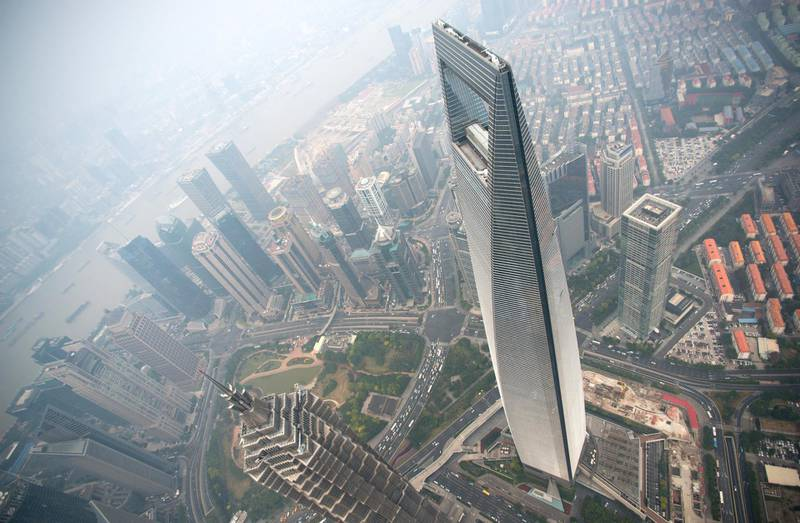 A general view shows the Shanghai World Financial Center and the skyline of the Lujiazui Financial District in Pudong, seen from the 109th floor of the Shanghai Tower (still under construction), covered in smog in Shanghai on October 16, 2014. China has for years been hit by heavy air pollution, caused by enormous use of coal to generate electricity to power a booming economy, and more vehicles on the roads. AFP PHOTO / JOHANNES EISELE (Photo by Johannes EISELE / AFP)