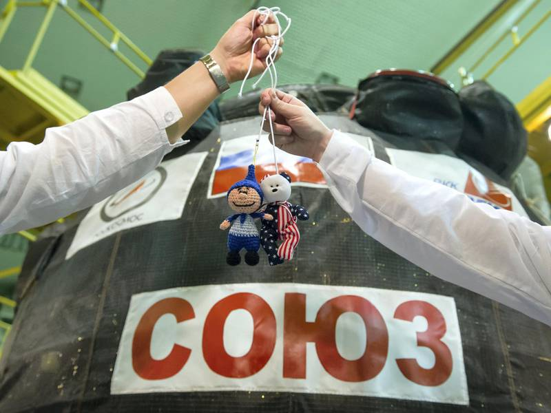 """jsc2017e096664 (July 17, 2017) --- In the Integration Facility at the Baikonur Cosmodrome in Kazakhstan, unidentified Expedition 52-53 crewmembers display toys from their children July 17 outside their Soyuz MS-05 spacecraft during a fit check dress rehearsal. The toys are hung above the crewmembers' heads in the Soyuz' descent module compartment as weightless, or """"zero-g"""" indicators during the launch phase of the mission. Randy Bresnik of NASA, Sergey Ryazanskiy of the Russian Federal Space Agency (Roscosmos) and Paolo Nespoli of the European Space Agency will launch July 28 on the Soyuz MS-05 spacecraft for a five-month mission on the International Space Station. Credit: Andrey Shelepin/Gagarin Cosmonaut Training Center"""