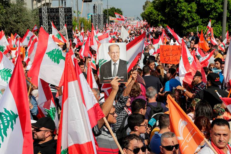 TOPSHOT - A supporter of Lebanese President Michel Aoun holds his picture during a counter-protest near the presidential palace in Baabda on November 3, 2019. Thousands of Lebanese gathered to show support to the embattled president, an AFP correspondent said, after more than two weeks of mass anti-graft protests that brought down the government. / AFP / ANWAR AMRO