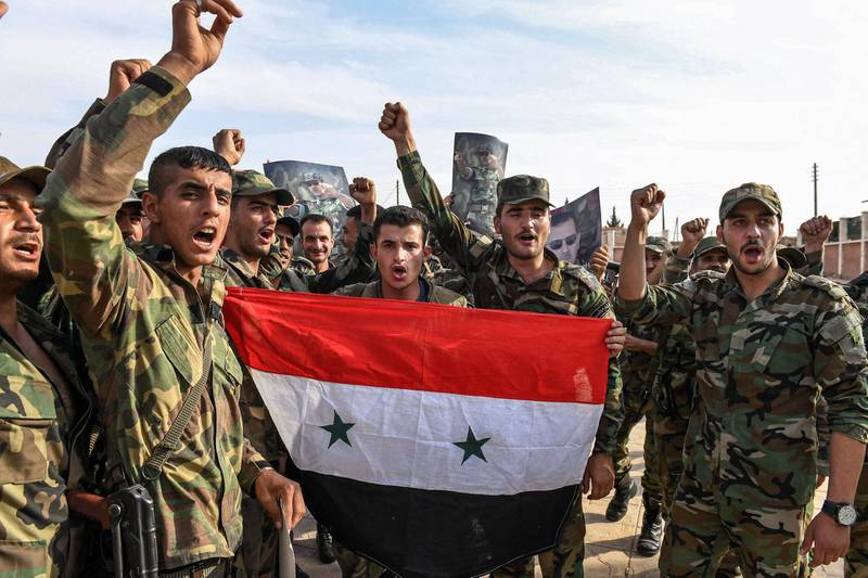 Syrian government soldiers chant slogans as they pose for a group photo with a national flag and portraits of President Bashar al-Assad near the outskirts of the northern city of Manbij in the north of Aleppo province as government forces deploy there on October 15, 2019.  / AFP / -