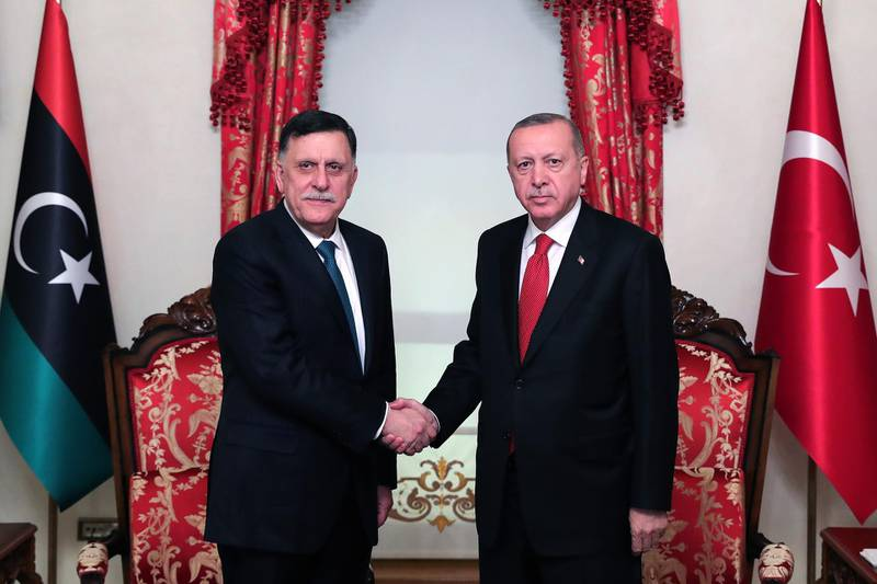 """A handout picture taken and released on November 27, 2019, by the Turkish Presidential Press service shows Turkish President Recep Tayyip Erdogan (R) shaking hands with Fayez al-Sarraj (L), the head of the Tripoli-based Government of National Accord (GNA), during their meeting in Istanbul. - Turkey signed a military deal late on November 27, 2019, with Libya's UN-recognised government following a meeting with Turkish President in Istanbul, his office said. (Photo by Mustafa Kamaci / TURKISH PRESIDENTIAL PRESS SERVICE / AFP) / RESTRICTED TO EDITORIAL USE - MANDATORY CREDIT """"AFP PHOTO / TURKISH PRESIDENTIAL PRESS SERVICE"""" - NO MARKETING - NO ADVERTISING CAMPAIGNS - DISTRIBUTED AS A SERVICE TO CLIENTS"""