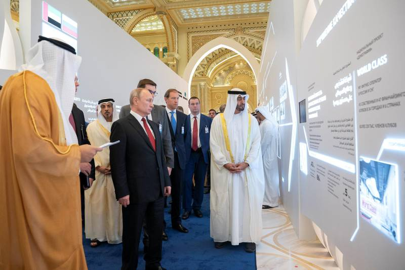 ABU DHABI, UNITED ARAB EMIRATES - October 15, 2019: HH Sheikh Mohamed bin Zayed Al Nahyan, Crown Prince of Abu Dhabi and Deputy Supreme Commander of the UAE Armed Forces (R) and HE Vladimir Putin Vladimirovich, President of Russia (C), view a UAE-Russia investment exhibition presented by Mubadala, during a state visit reception at Qasr Al Watan.Seen with HH Sheikh Mansour bin Zayed Al Nahyan, UAE Deputy Prime Minister and Minister of Presidential Affairs (L).  ( Hamad Al Kaabi / Ministry of Presidential Affairs ) ---