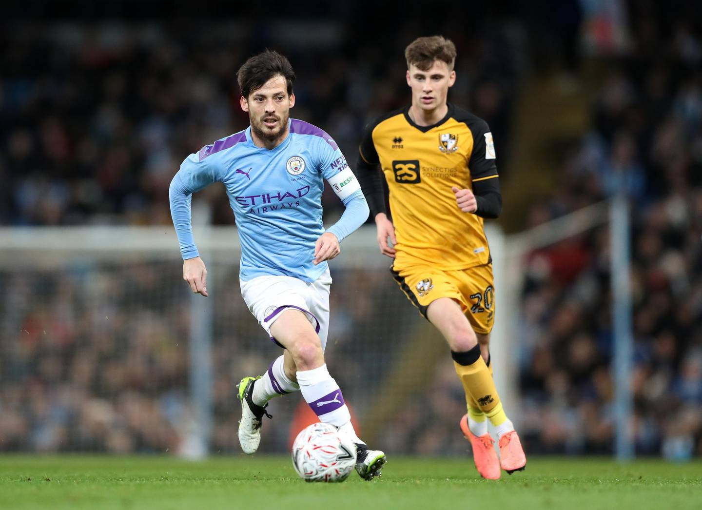 MANCHESTER, ENGLAND - JANUARY 04: David Silva of Manchester City runs with the ball under pressure from Scott Burgess of Port Vale during the FA Cup Third Round match between Manchester City and Port Vale at Etihad Stadium on January 04, 2020 in Manchester, England. (Photo by Alex Livesey/Getty Images)