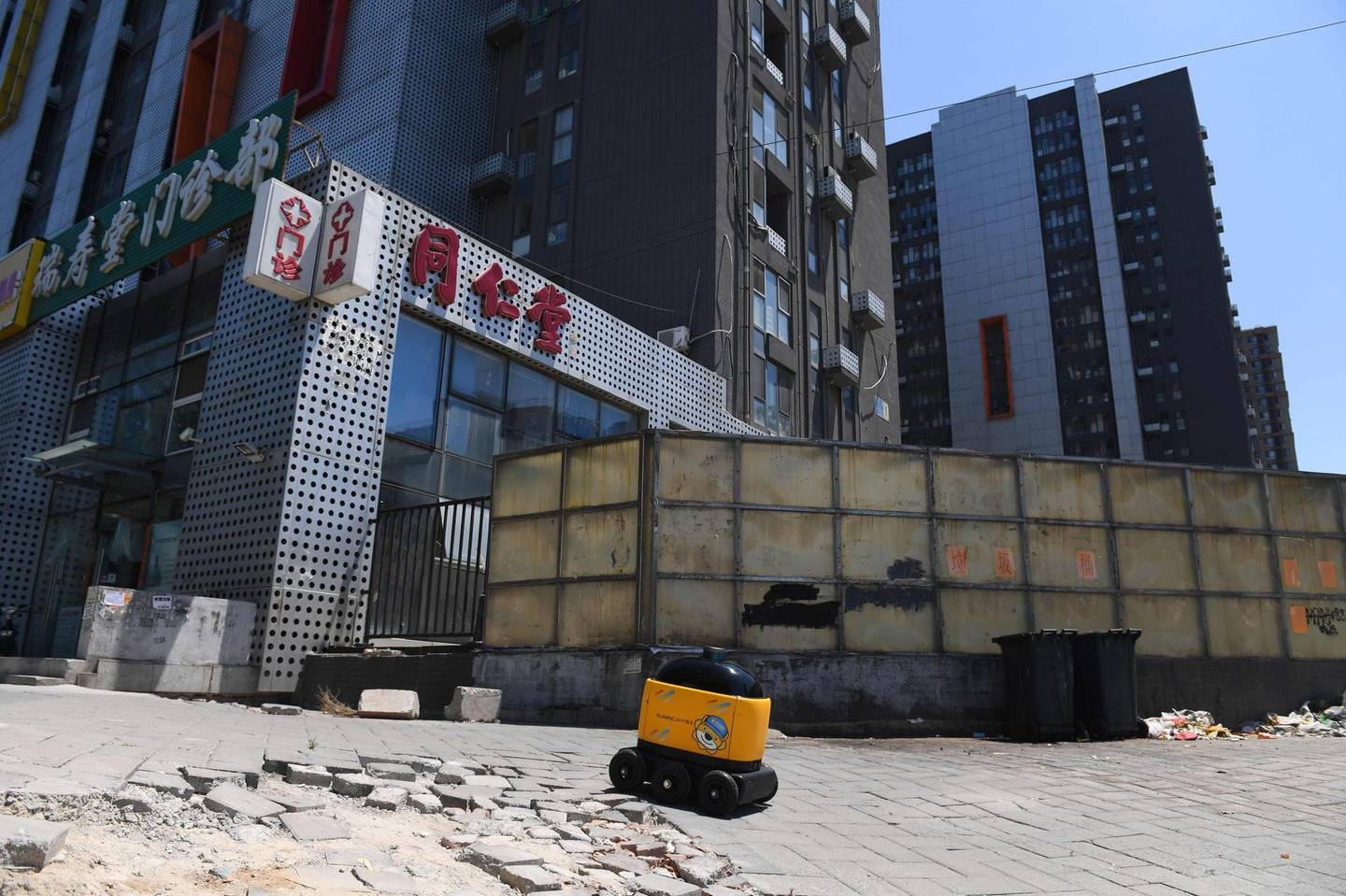 """A Zhen Robotics delivery robot makes its way from a Suning supermarket to a residential compound during a demonstration of the robot in Beijing. Along a quiet residential street on the outer edges of Beijing, a yellow and black cube about the size of a small washing machine trundles leisurely to its destination. This """"little yellow horse"""" is an autonomous delivery robot, ferrying daily essentials like drinks, fruit and snacks from the local store to the residents of the """"Kafka"""" compound in the Chinese capital.  - TO GO WITH AFP STORY CHINA-TECHNOLOGY-ROBOTS-CONSUMER-SCIENCE,FEATURE BY LUDOVIC EHRET  / AFP / GREG BAKER / TO GO WITH AFP STORY CHINA-TECHNOLOGY-ROBOTS-CONSUMER-SCIENCE,FEATURE BY LUDOVIC EHRET"""